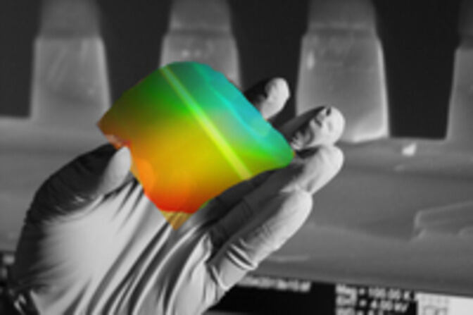 flexible substrate showing rainbow colors held by a gloved hand